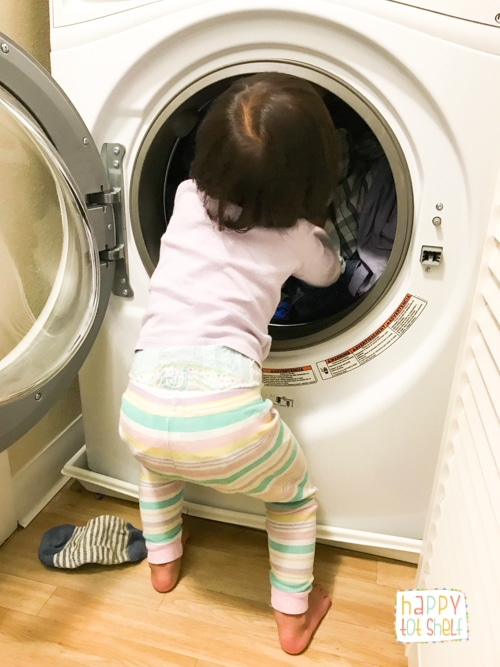 Toddler putting laundry into washer