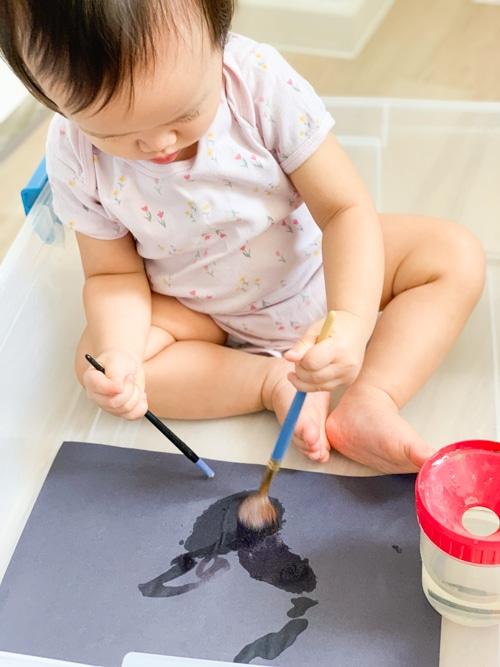 Simple art activity for 1 year old - painting with water on black paper