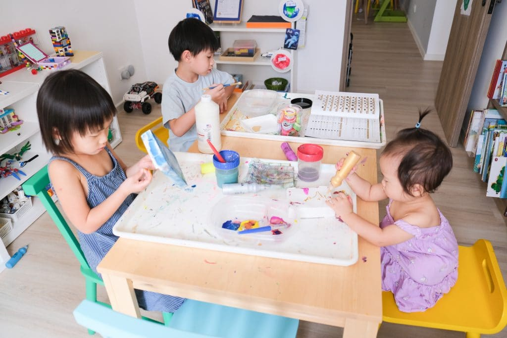 Children painting and making art at table in a room