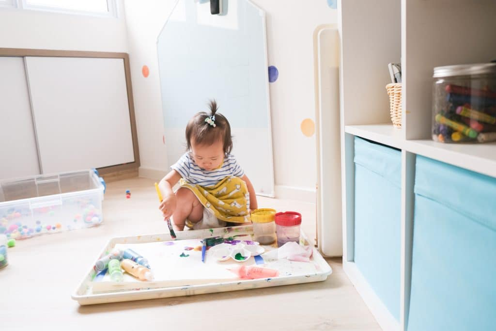 Toddler painting on a big tray