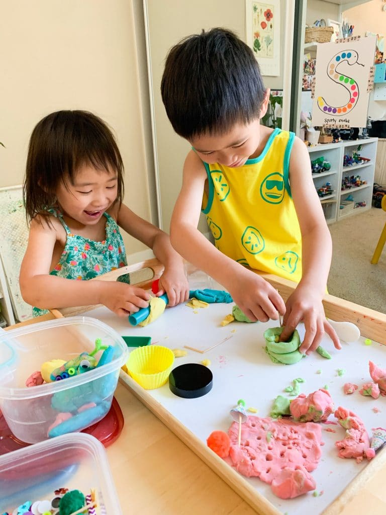 Two children playing with play dough on a big tray